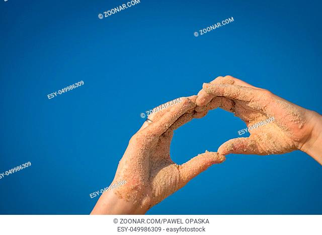 Close up of a sand covered woman hand making the heart shape with blue sky background