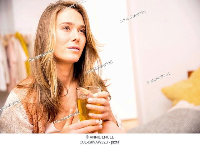 Mid adult woman sitting on bed drinking herbal tea