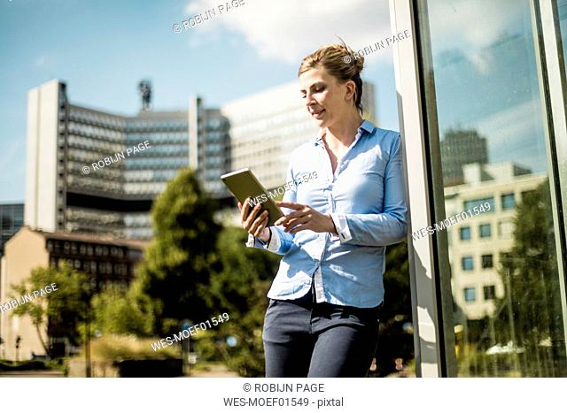 Smiling woman leaning against a building using tablet
