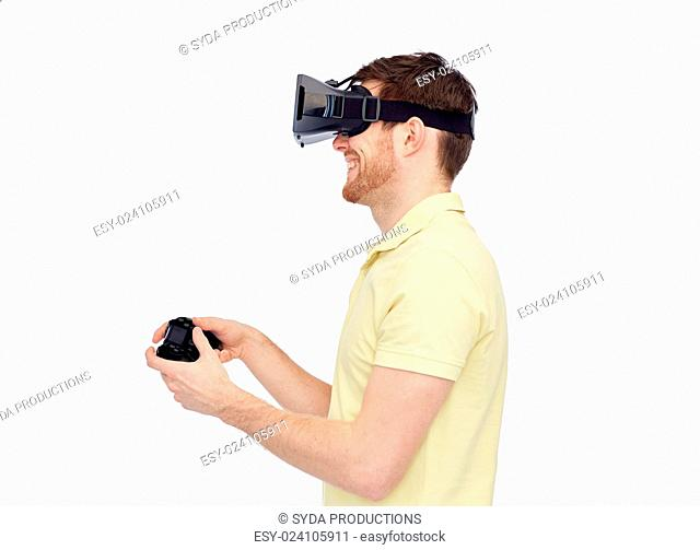 3d technology, virtual reality, entertainment and people concept - happy young man with virtual reality headset or 3d glasses playing with game controller...