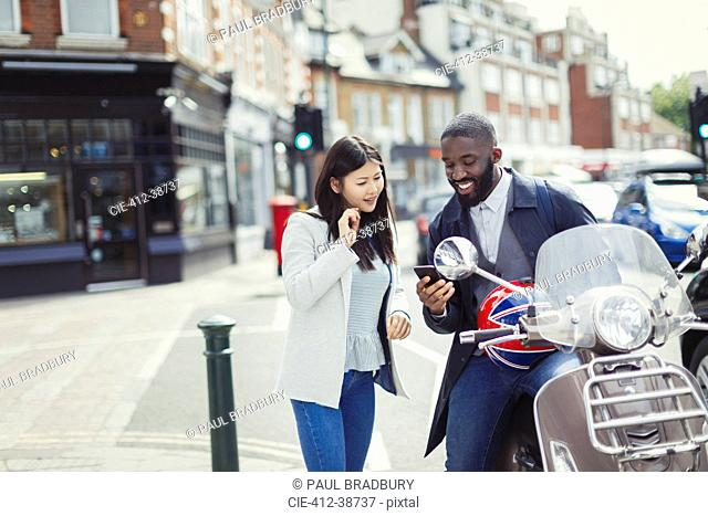 Young couple using cell phone at motor scooter on sunny urban street