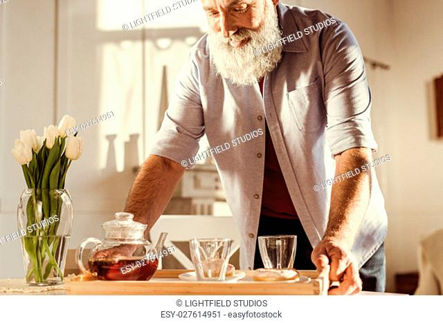 Senior man holding tray with tea and sweets and smiling