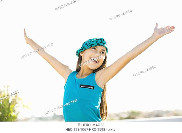 Girl with arms raised outdoors