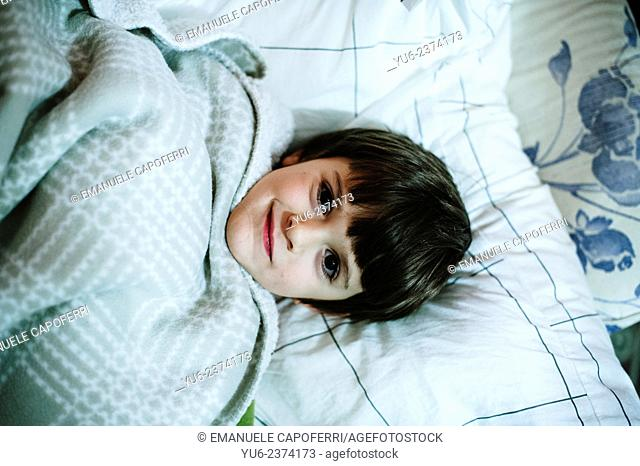 Child resting under the covers