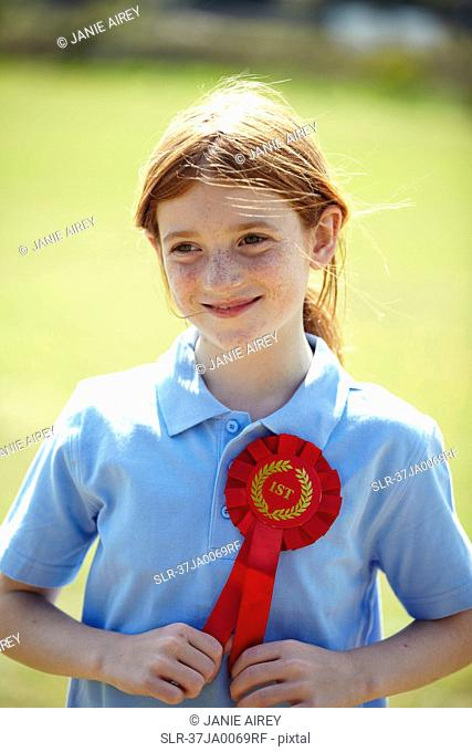 Smiling girl wearing first place ribbon