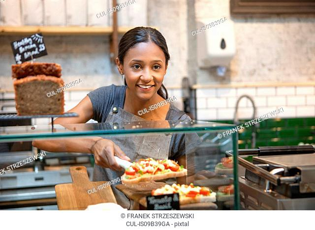 Waitress serving open sandwich from cafe display cabinet