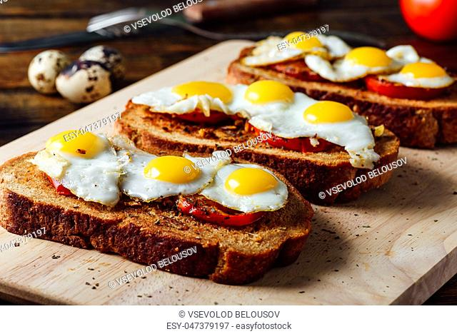 Toasts with Fried Quail Eggs on Cutting Board
