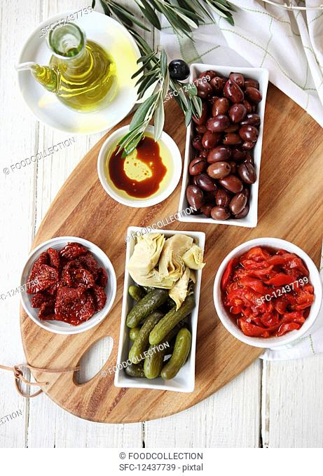 Antipasto dish - sun-dried tomatoes and capsicum, kalamata olives, gherkins, artichokes, Bread rolls, olive oil (with balsamic vinegar)and olive branch