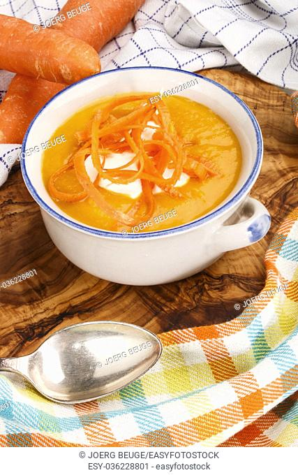 warm carrot curry soup with sour cream in a bowl