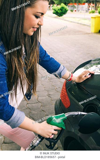 Hispanic woman fueling car in gas station