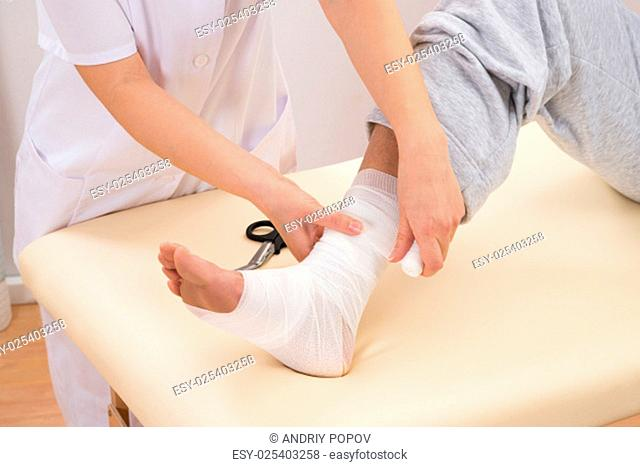 Close-up Of A Woman Tying Bandage On Patient's Foot