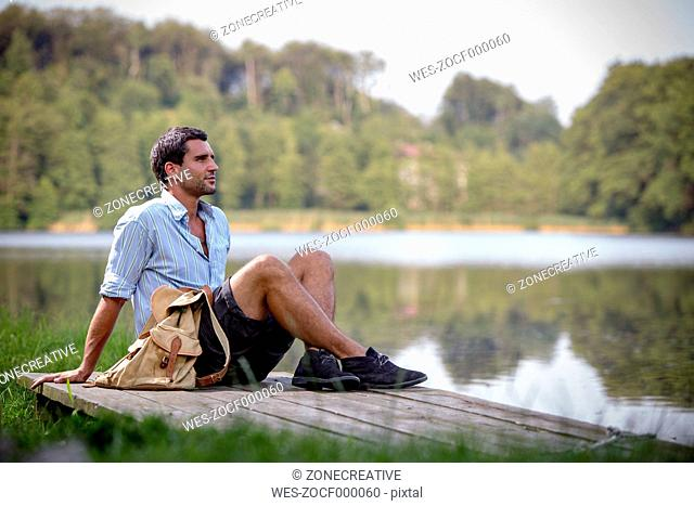Portrait of young man sitting on a jetty at lake