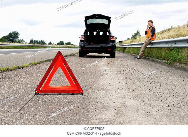 Stranded motorist, sitting on the crash barrier on the hard shoulder of a motorway, calling assistance for his broken down car, taking the necessary precautions