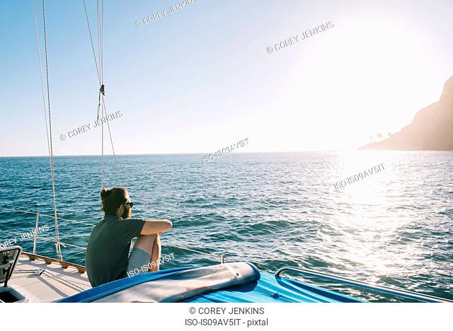 Man enjoying sunset on sailboat, San Diego Bay, California, USA