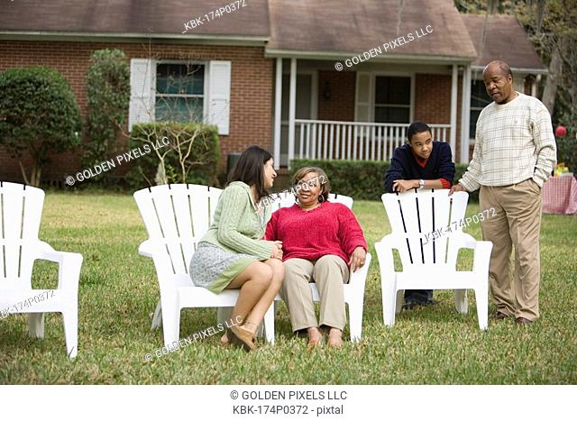 Family and friend relaxing in backyard conversing