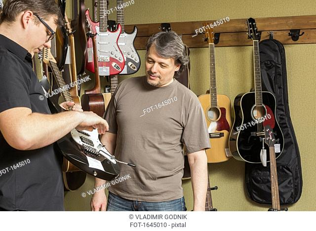 Mature male owner looking at young man examining electric guitar at store