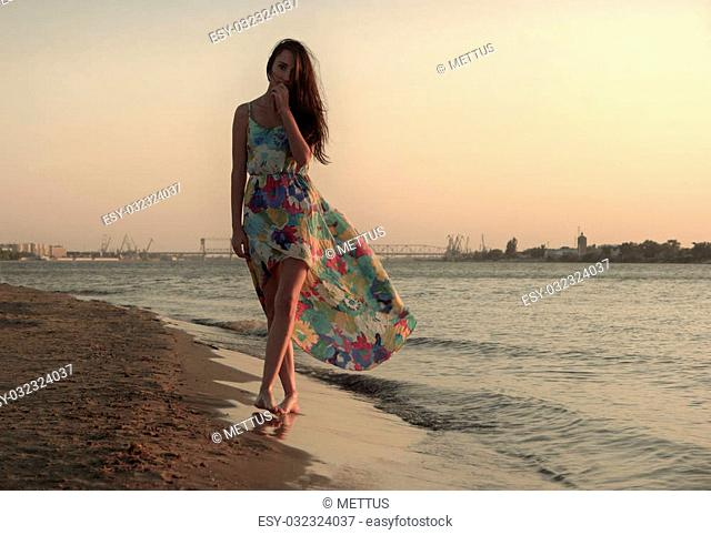 Young woman in a colorful dress on the ocean coast a lot of space for text