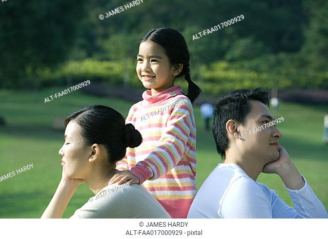 Couple sitting back to back, daughter standing behind them with hand on mother's shoulder