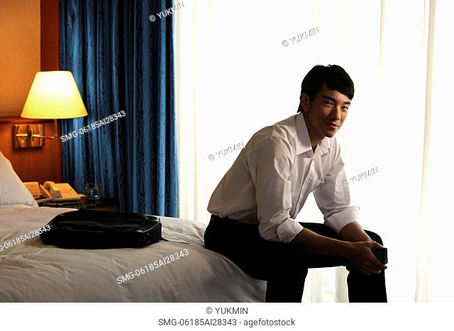 Young man sitting on edge of bed in hotel room