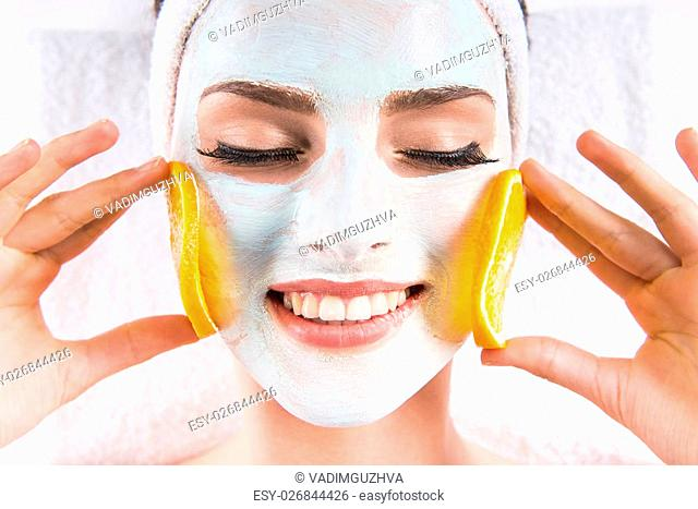 Young beautiful woman holding orange slices and mask on the face in a spa salon