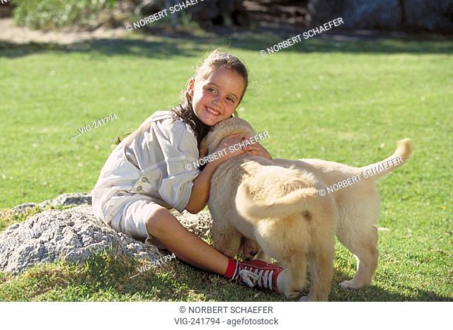 full-figure, 8 -year-old girl with long brown hair wearing white short trousersand red basketball-boots plays with her two little dogs on a meadow  - GERMANY