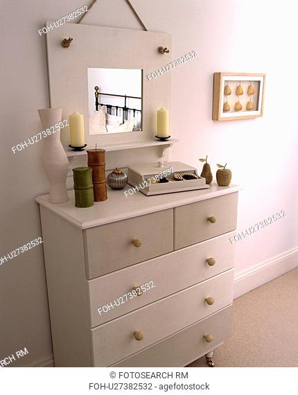 Painted mirror and chest of drawers in a modern white bedroom