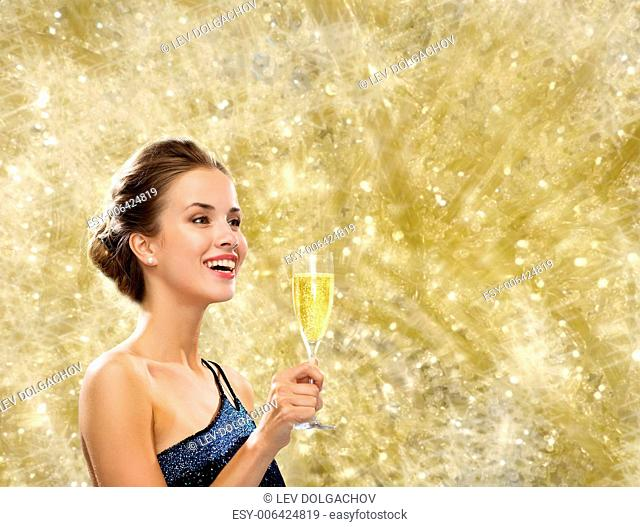 party, drinks, holidays, luxury and celebration concept - smiling woman in evening dress with glass of sparkling wine over yellow lights background