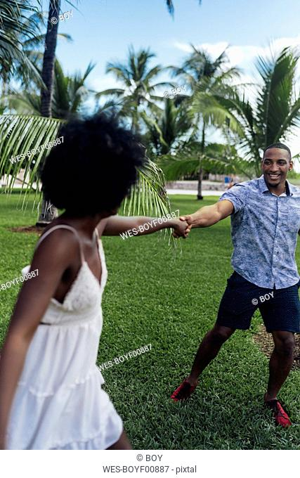 USA, Florida, Miami Beach, happy young couple dancing in a park in summer