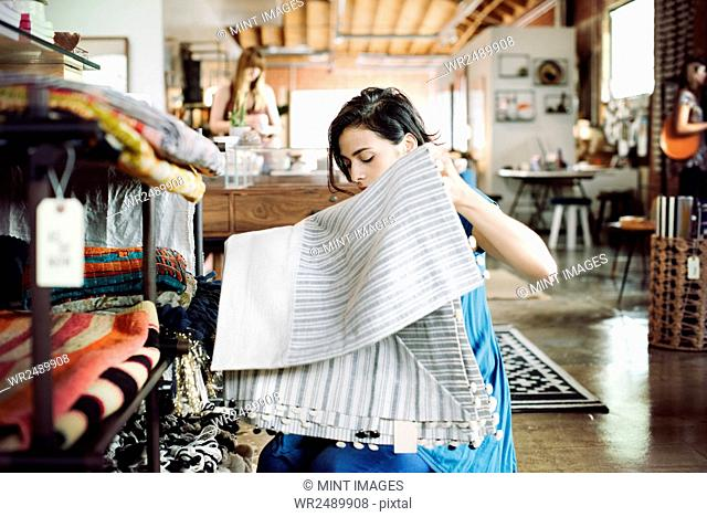 Young woman in a shop, holding a striped tablecloth