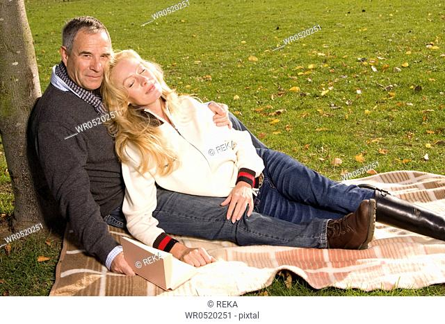 Mature couple sitting on blanket in park