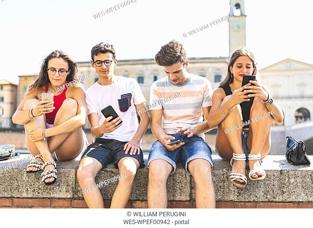 Italy, Pisa, group of four friends sitting together on a wall using cell phones
