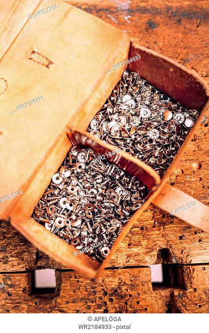 Directly above shot of tool bag filled with nuts on table at workshop