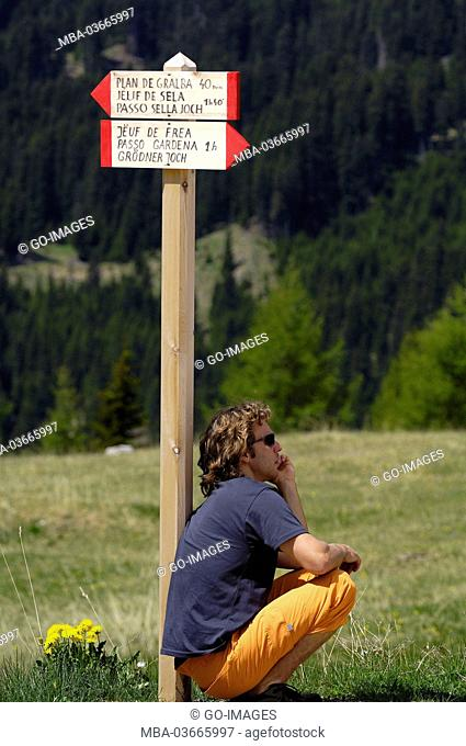 Young man leans against signpost, the Dolomites