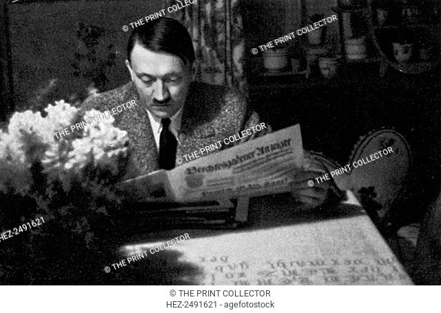 Adolf Hitler in the evening at Obersalzberg, Bavaria, Germany, 1936. Hitler (1889-1945) relaxing with the newspaper at his mountain retreat, the Berghof