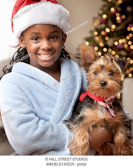 Smiling Black girl in Santa hat holding small dog