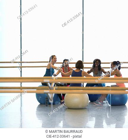 Smiling women holding hands on fitness balls in gym studio