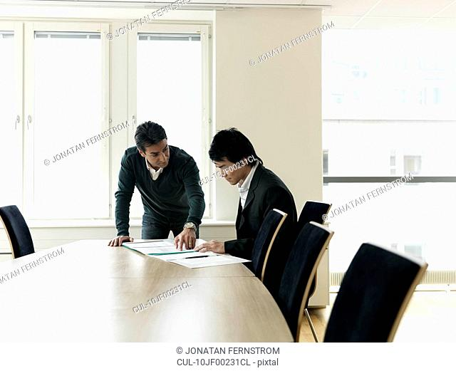 Business colleagues by conference table