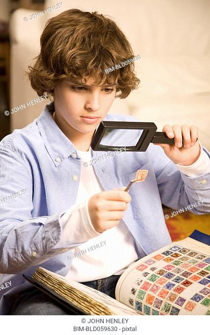 Hispanic boy examining stamp through magnifying glass
