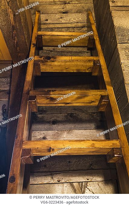 Pinewood Miller's stairs in attic bedroom leading to bed located on the mezzanine inside an old circa 1752 Canadiana style fieldstone house