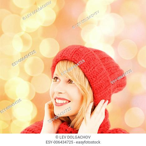 happiness, winter holidays, christmas and people concept - smiling young woman in red hat and scarf over beige lights background