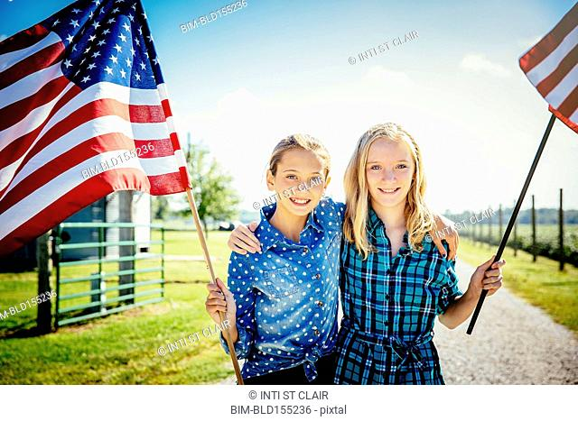 Caucasian girls waving American flags on farm