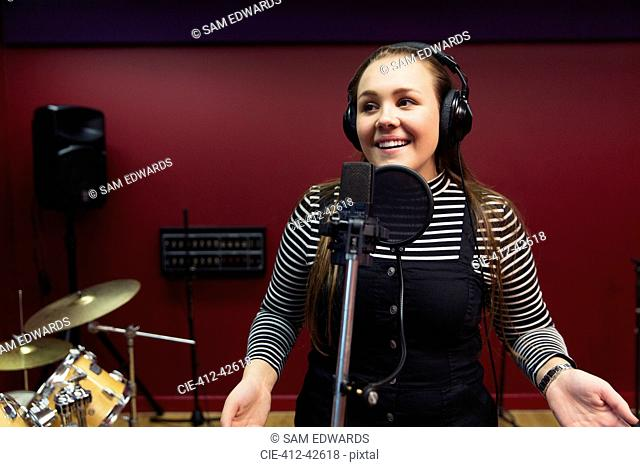 Confident teenage girl recording music, singing in sound booth
