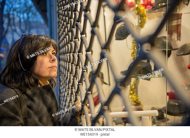 Woman Watching a Store Window With Metal Grate at Night in Antibes in Provence-Alpes-Côte d'Azur, France