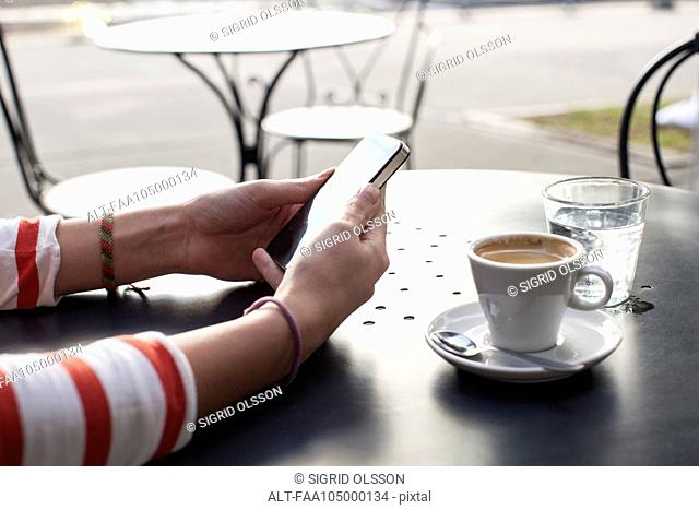 Young woman using smartphone in cafe, cropped