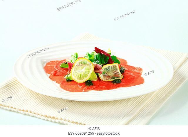 Beef Carpaccio with pesto, salad greens and Parmesan