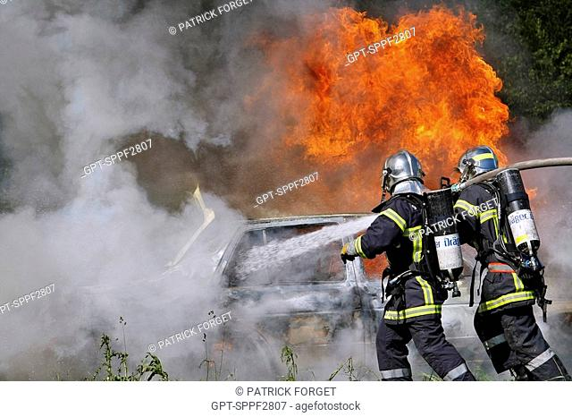 FIREFIGHTERS ATTACKING A FIRE ON THE SIDE PARTS OF THE CAR. TRAINING IN OPEN-AIR CAR FIRES, GASOLINE AND LPG LIGHT PETROLEUM GAS, VANNES, MORBIHAN 56, FRANCE