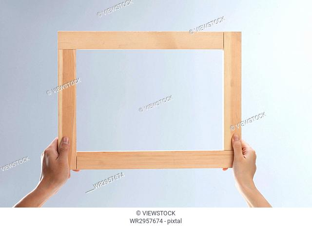 Hand holding a wooden frame