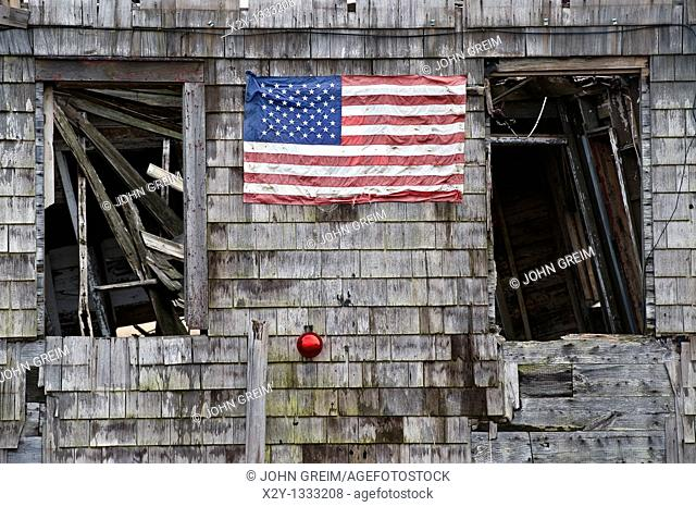 Christmas ornament and American flag on the the side of an abandoned house