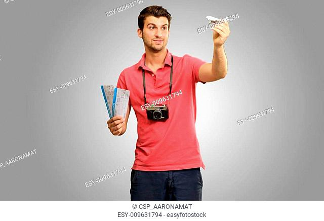 Young Man Holding Airplane And Boarding Pass