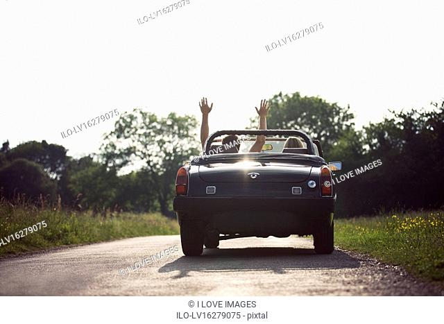 A young couple driving in a convertible black sports car, man with his arms in the air